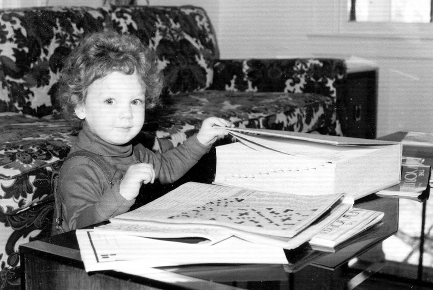 Girl with a mop of curly hair opening a big-ass dictionary.